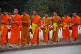 The monks from the peninsula temples walk along Thanon Xieng Thong