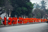 Long line of orange robed monks proceeding down Thanon Xieng Thong