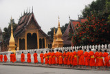 Monk procession passing a temple, Luang Prabang