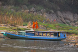 Monks along the Mekong with a boat