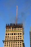 A fire on top of a building under construction