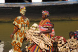Woman in colorful dress carrying firewood and a baby