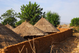 Walled compound with 3 thatched huts