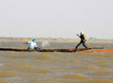 Man puts his weight behind the pole while another bails out the pirogue