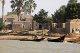 Mudbrick village with palm trees and fishing boats, Niger River, Mali