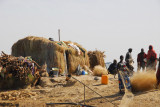 Fisher people preparing their nets by a grass hut, Niger River, Mali
