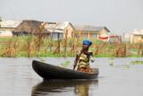 Ganvié woman paddling - no smile, no greeting