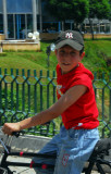 Boy on a bike with a NY Yankees hat, Hama