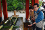 Tan, from Chiang Mai, Thailand, washing his hands at the shrine