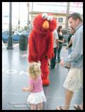 Elmo taking money from a little girl.
