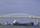 A Lake Freighter (Laker) steams from Lake Huron under the blue Water bridge into St  Clair river at Port Huron.