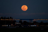 2014 - a large full moon rising on Valentine's Day over the approach lights for runway 9L at Opa-locka Executive Airport