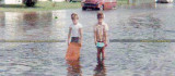 Early 1960's - closeup of two young boys playing on a flooded Hialeah street