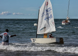 As the Optimist yachts come ashore after the racing the parents are there to help stop the yachts running ashore in the shallows