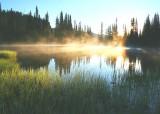 Sunlit dawn mist at Reflection Lake