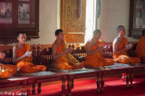 Buddhist monks conduct a ceremony of worship inside Wat Phra Singh
