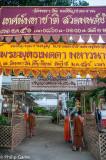 Monks hang up banners in Thai and Shan languages at Wat Mahawan