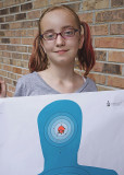 GRANDDAUGHER KATIE SHOWS OFF ONE OF HER TARGETS, AFTER A RECENT OUTING TO THE SHOOTING RANGE