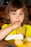 Blowing bubbles in her juice