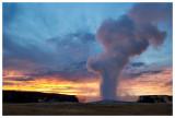 Old Faithful eruption at sunset