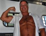 gay older man flexing massive biceps.jpg