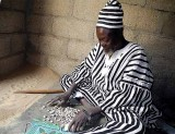 Healer Ba Zane (Mossi tribe) in Sena, Burkina Faso, writes magic words in the sand and throws cowries to help his clients.