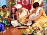 The waters of two coconuts are poured together on a plate by the bride's father; wedding ceremony in Karnataka, India