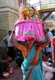 Devotee carrying a basket containing a brass bust of Yellamma, Yellamma temple,  Saundatti, Karnataka, India