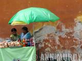 Vendor with green umbrella