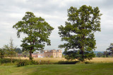 CC013. A view of Croome Court through the tree by the lake.