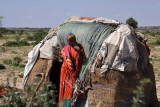 Somali woman in front of her small hut