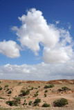 White puffy clouds in the blue sky over the desert hills