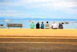 Visitors sitting on wall at Kaiteriteri web.jpg