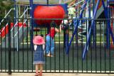 A child in pink hat watching children play