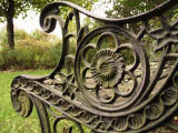 Weathered wrought iron bench arm