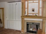 A cabinet appears next to the yet unfinished fireplace mantle
