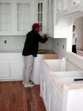 An installer works on the custom cabinets