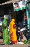 Women in saris and a vegetable vendor