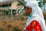 Indonesian woman watches as relief supplies come in