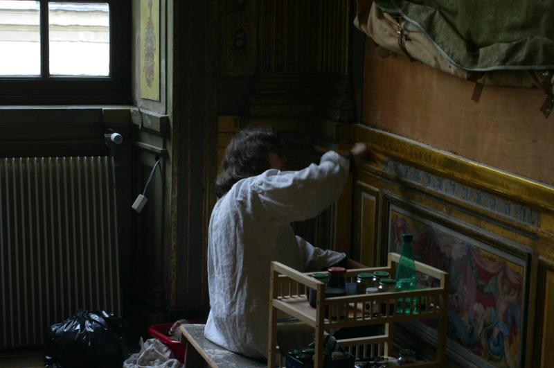 An artisan restoring the gold-leaf woodwork