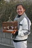 Une jeune fille promène son oiseau dans les rues de Pékin