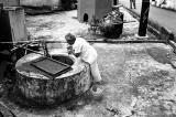 Elderly Villager Drawing Water from Well