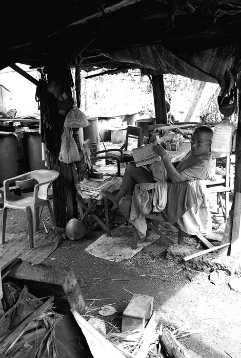 Elderly Villager Reading Newspaper