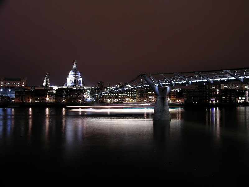 Londons Millenium Bridge and St Pauls, cruise ship sailing past.