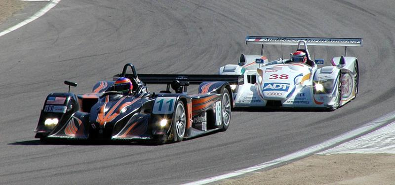 A Lola and an Audi leave turn 3