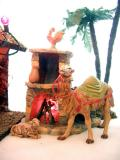 The Magis' camel (added in '01) and one of the sheep warm themselves by the fireplace