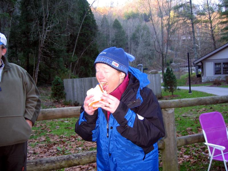 Mary enjoys a sandwich after finishing in 8:04