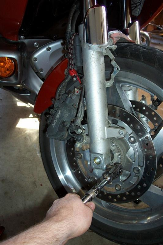 Loosening axle clamp bolts. Notice caliper is supported with bungee to reduce stress on brake lines.