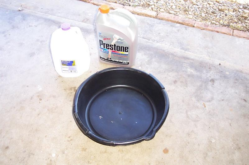 New antifreeze, distilled water, and clean drain pan at the ready