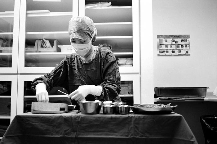 Scrub Nurse Preparing Surgical Instruments